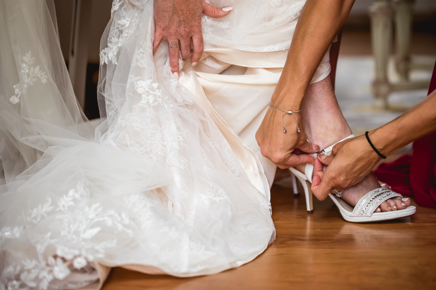 Bride adjusting shoes in wedding dress
