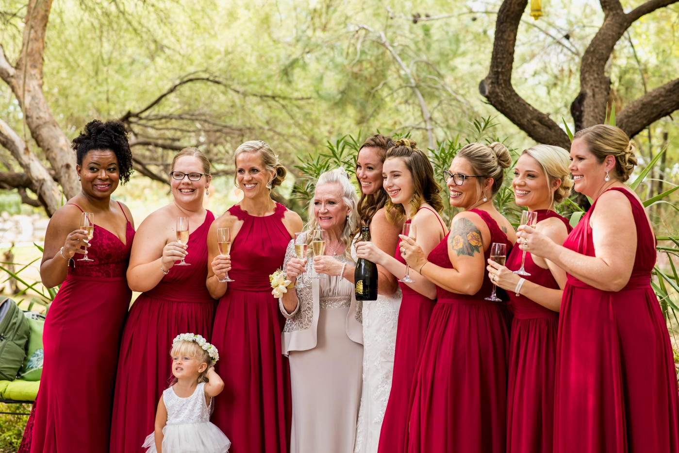 bridal party wearing red dresses against a mesquite tree